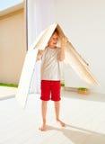 在家使用与纸板箱的逗人喜爱的愉快的男孩 库存图片