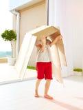 在家使用与纸板箱的逗人喜爱的愉快的男孩 免版税库存图片
