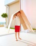 在家使用与纸板箱的逗人喜爱的愉快的男孩 图库摄影