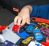 在家使用与葡萄酒玩具汽车的年轻男孩 选择聚焦在手边男孩和玩具 免版税库存照片