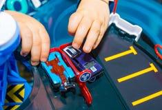 在家使用与葡萄酒玩具汽车的年轻男孩 选择聚焦在手边男孩和玩具 免版税库存图片