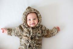 在家使用与软的玩具熊玩具的小男婴,躺下 免版税库存图片