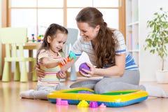在家使用与运动沙子的儿童小女孩和母亲 免版税库存照片
