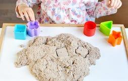 在家使用与运动沙子的小女孩 免版税图库摄影
