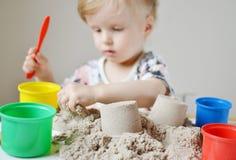 在家使用与运动沙子的小女孩 免版税库存照片