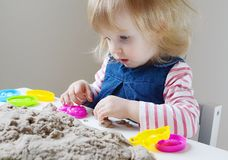 在家使用与运动沙子的小女孩 库存照片