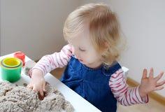 在家使用与运动沙子的小女孩 免版税库存图片