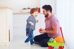 在家使用与逗人喜爱的小孩小儿子的愉快的父亲,家庭比赛 免版税库存图片
