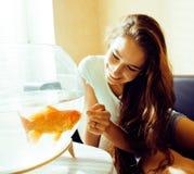 在家使用与金鱼的俏丽的妇女,阳光早晨愉快的生活方式 免版税库存照片