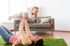 在家使用与婴孩的愉快的年轻母亲 免版税图库摄影