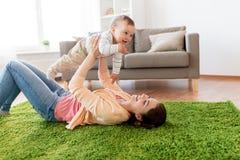在家使用与婴孩的愉快的年轻母亲 库存图片