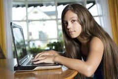 在家使用便携式计算机的女孩 免版税图库摄影