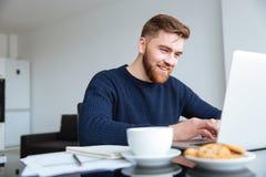 在家使用便携式计算机的微笑的人 库存照片