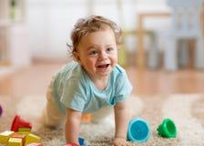在家使用和爬行在地板上的小男婴 图库摄影
