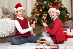在家使用圣诞老人的帽子的孩子获得乐趣和,圣诞节装饰,愉快的情感,寒假概念 库存照片