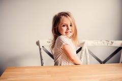 在家使用在厨房里的愉快的逗人喜爱的小孩女孩 免版税库存图片