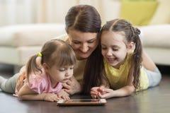 在家使用在地板上的愉快的妇女和孩子数字式片剂 免版税库存照片