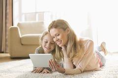 在家使用在地板上的母亲和女儿数字式片剂 免版税库存图片
