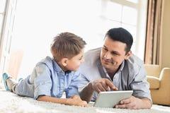 在家使用在地板上的父亲和儿子数字式桌 库存图片