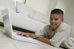 在家使用在地板上的男孩的画象膝上型计算机 库存照片
