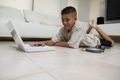 在家使用在地板上的男孩膝上型计算机 免版税库存图片