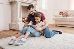 在家使用在地毯的不同种族的父亲和女儿数字式片剂 库存图片
