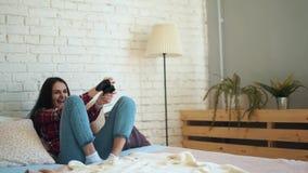 在家使用在床上的一个控制台的女孩 生活方式和技术的概念 股票视频