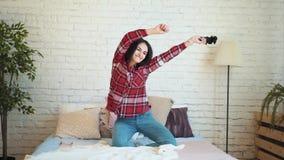 在家使用在床上的一个控制台的女孩 生活方式和技术的概念 影视素材
