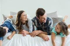 在家使用在床上的家庭在卧室 库存照片
