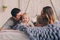 在家使用在床上的愉快的家庭 母亲、父亲和婴孩生活方式捕获  库存图片