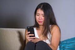 在家使用在手机微笑的放松的开会的年轻甜愉快和相当亚裔韩国妇女互联网社会媒介app如此 免版税库存照片