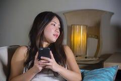 在家使用在手机微笑的放松的开会的年轻甜愉快和相当亚裔韩国妇女互联网社会媒介app如此 库存照片