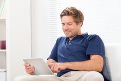 在家使用在沙发的人数字式片剂 免版税库存照片