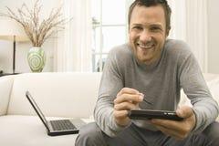 在家使用在沙发的人片剂和计算机。 免版税库存图片