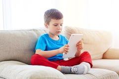 在家使用在沙发的小男孩片剂 免版税库存照片