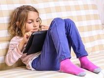 在家使用在片剂个人计算机的小女孩 库存图片
