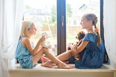 在家使用在窗口附近的两个逗人喜爱的欧洲小孩女孩 库存照片