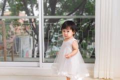 在家使用在窗口附近的小逗人喜爱的亚裔女婴 库存图片