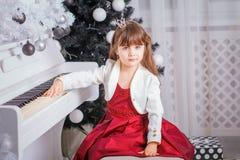 在家使用在钢琴的圣诞节儿童小女孩 免版税库存图片