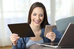 在家使用在长沙发的妇女多个设备 免版税库存图片