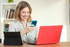 在家使用多个设备的白肤金发的妇女 免版税库存照片