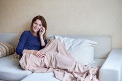在家使用她在长沙发的少妇巧妙的电话在客厅 库存照片