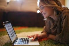 在家使用她的膝上型计算机的白肤金发的妇女 库存图片
