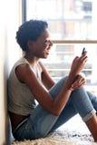 在家使用巧妙的电话的年轻黑人妇女由窗口 免版税图库摄影
