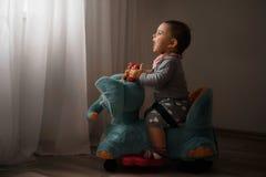 在家使用户内在大象玩具幸福的记忆的todler婴孩低灯照片 免版税库存图片