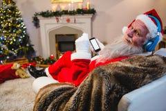 在家使用手机的圣诞老人 库存图片
