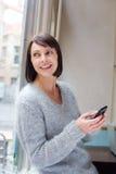 在家使用手机的微笑的老妇人 免版税库存照片
