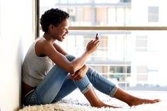 在家使用手机的愉快的年轻非裔美国人的妇女由窗口 库存照片