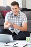 在家使用手机的男性自由职业者的工作者画象  免版税库存图片