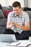 在家使用手机的男性自由职业者的工作者 免版税库存照片